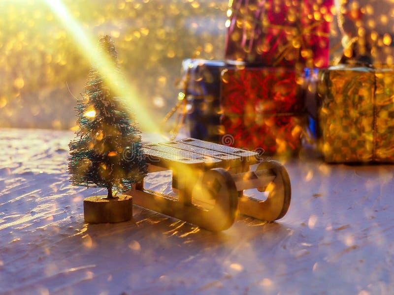 Kerstmisstilleven van een stuk speelgoed slee, Uitstekende foto, Giften voor Kerstmis op houten slee, Vrolijke Kerstboomvervoerde royalty-vrije stock afbeelding
