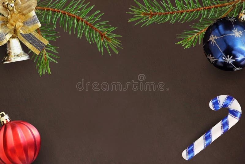 Kerstmistakken van sparren, stok, blauwe en rode ballon en decoratieve klok op donkere achtergrond royalty-vrije illustratie