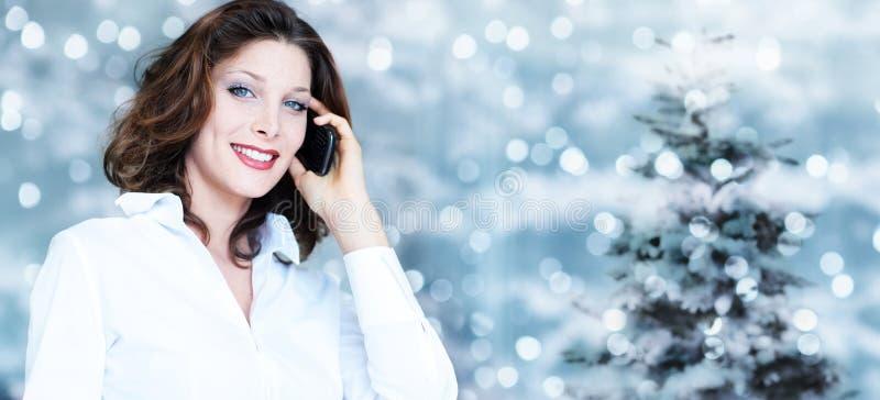 Kerstmisthema, bedrijfs glimlachende vrouw die smartphone op vage verstralers gebruiken royalty-vrije stock afbeelding