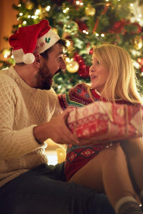 Kerstmistraditie - Vrolijk paar die met gift op Chri genieten van royalty-vrije stock fotografie