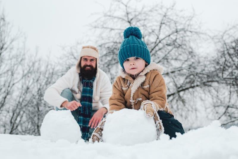 Kerstmisvakantie en de winter nieuw jaar met vader en zoon Gelukkige vader en zoon die sneeuwman in de sneeuw maken handmade stock afbeeldingen