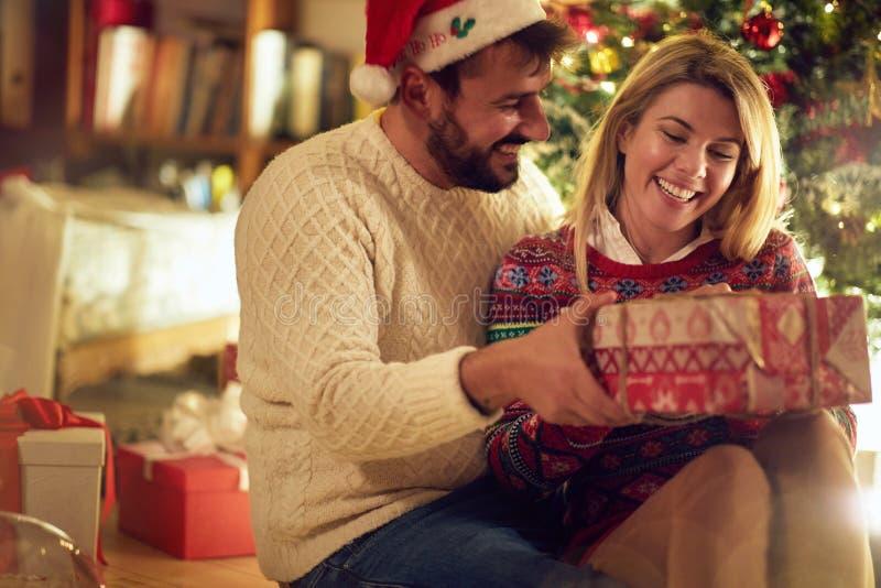 Kerstmisvakantie - Vrolijk paar die met gift op Christus genieten van stock afbeelding