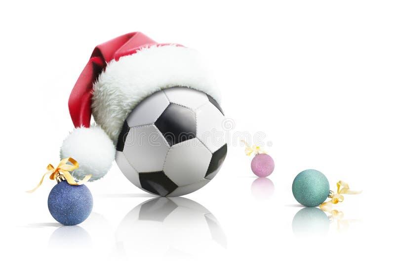 Kerstmisvoetbal Voetbalbal in Kerstmisspeelgoed van de santahoed op een witte achtergrond Geïsoleerde royalty-vrije stock afbeeldingen