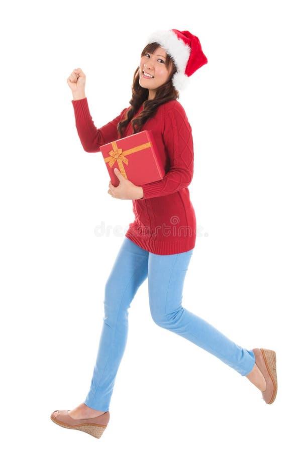 Kerstmisvrouw die met gift lopen stock afbeeldingen
