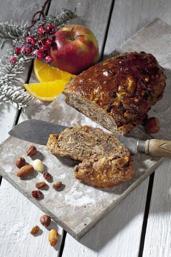 Kerstmisvruchtencake met noten en vruchten en Kerstmisdecoratie op houten raad royalty-vrije stock foto