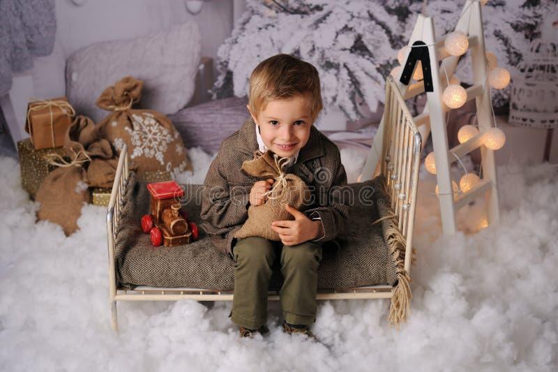 Kerstmiszitting van een jongen in het bos stock afbeeldingen