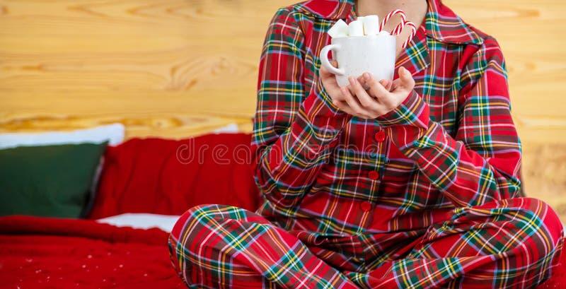 Kerstmorgen, meisje in pyjama's met een kopje hete cacao met marshmallows Selectieve focus royalty-vrije stock fotografie