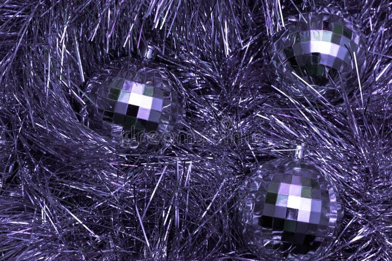 Kerstspeelgoed in de vorm van disco-ballen ligt op een feestelijk zilveren blik, bovenaanzicht, paarse kleur stock foto