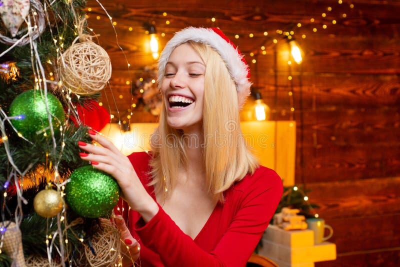Kerstspeelgoed - sensueel meisje versiert de kerstboom Vrouw in kerstjurk met bauble in de buurt van Kerstmis stock afbeeldingen