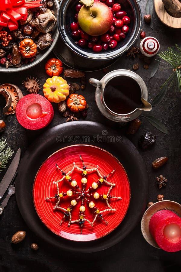 Kersttafel op donkere, bijtende tafelachtergrond met brandende kaarsen, rode plaat, versiering van sneeuwvlokken, saus, gedroogd royalty-vrije stock foto's