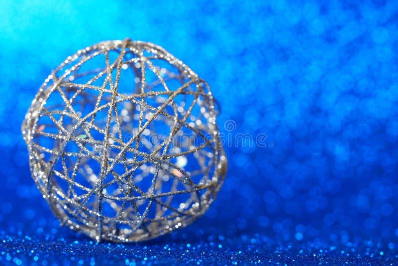 kerstversiering - een bol zilveren draad ligt op een mousserende blauwe achtergrond De langverwachte wintervakantie Blanco voor n stock foto