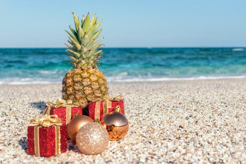 kerstversieringen, bubbels en ananas op een zandstrand op een zonnige en zonnige dag Nieuwjaarsconcept royalty-vrije stock afbeelding