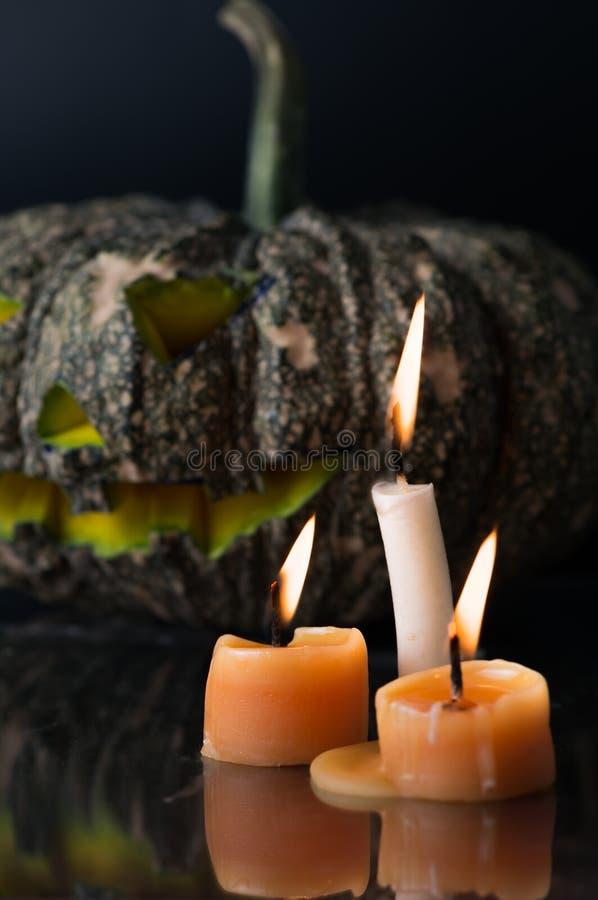 Kerze auf Halloween-Kürbiskopfsteckfassungs-Laternenhintergrund in der Dunkelheit lizenzfreies stockfoto