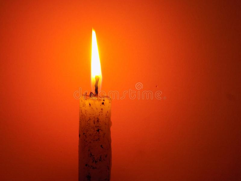 Kerze beleuchtet mit orange Hintergrund lizenzfreies stockbild