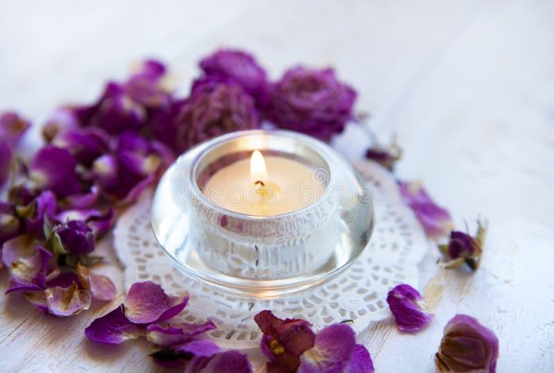 Kerze in den getrockneten rosafarbenen Blumenblättern aromatherapy lizenzfreie stockbilder