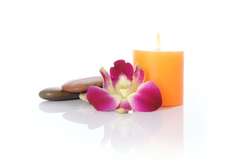 Kerze, Fluss-Steine und Orchidee lizenzfreie stockbilder