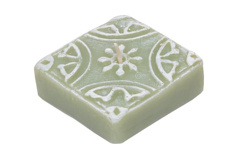 Kerze getrennt Nahaufnahme einer grünen quadratischen Kerze mit dem weißen Muster lokalisiert auf einem weißen Hintergrund lizenzfreies stockfoto