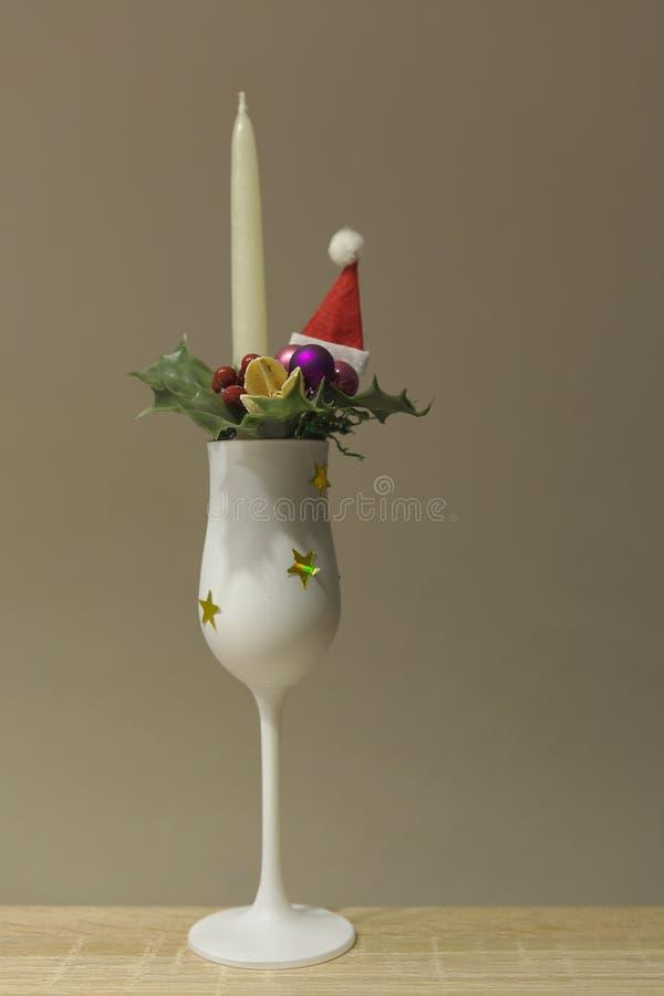 Kerze im Champagnerglas mit Weihnachtsdekoration stockbild