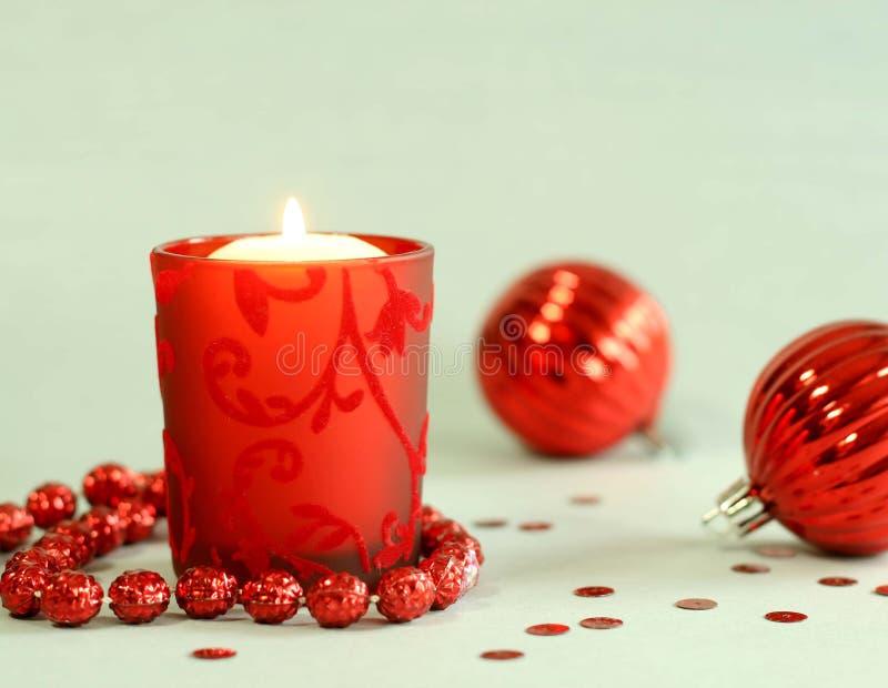 Kerze im schönem rotem Kerzenhalter und in Christ stockfotografie