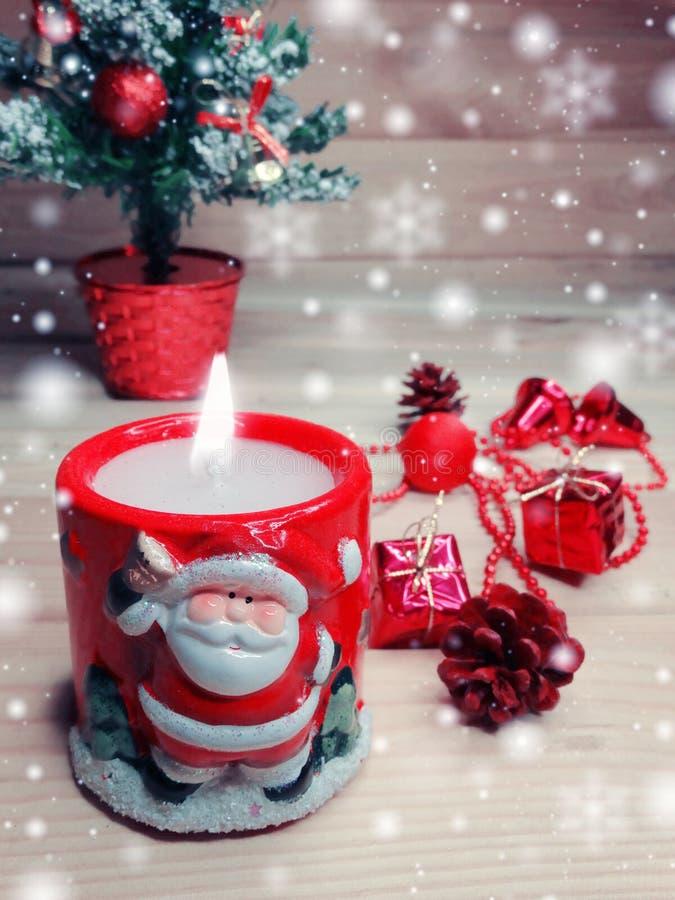 Kerze mit Sankt-Weihnachtsdekoration und Schnee auf hölzernem backgr lizenzfreie stockfotos