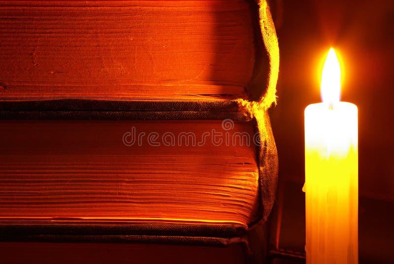 Kerze nahe Büchern lizenzfreies stockfoto