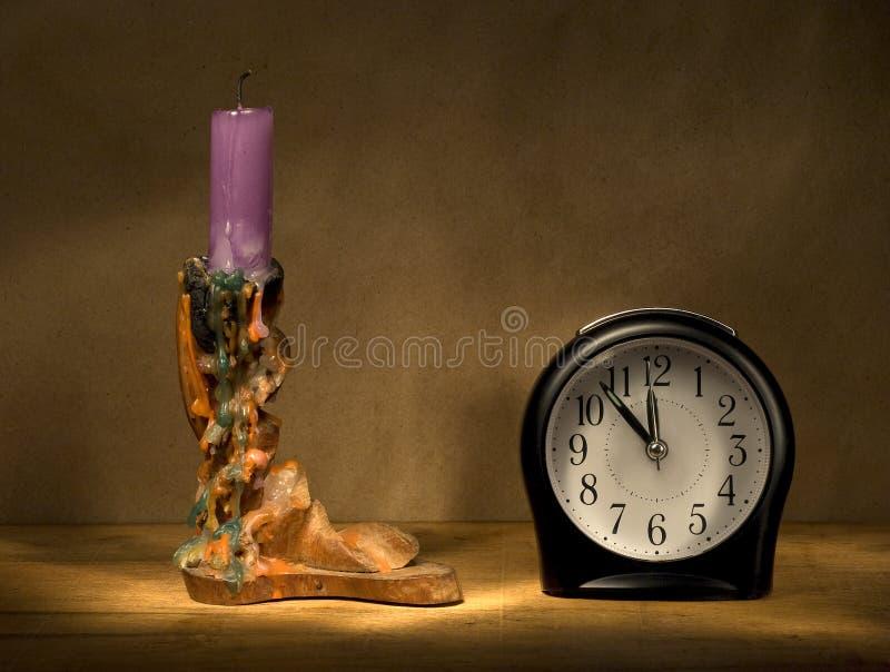 Kerze und Alarmuhr. stockbild