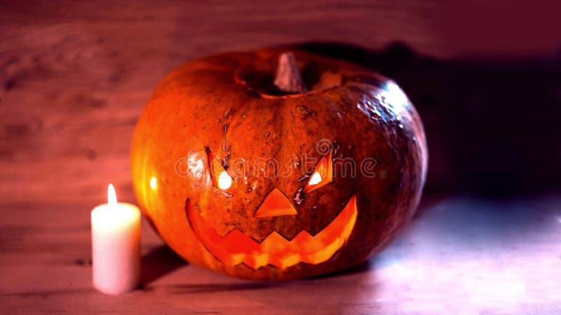 Kerze und ein gruseliger l?chelnder Halloween-K?rbis auf einem Holztisch stockfotos