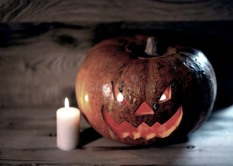 Kerze und ein gruseliger l?chelnder Halloween-K?rbis auf einem Holztisch lizenzfreies stockbild