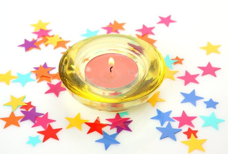 Kerze und farbige Sterne lizenzfreie stockfotografie