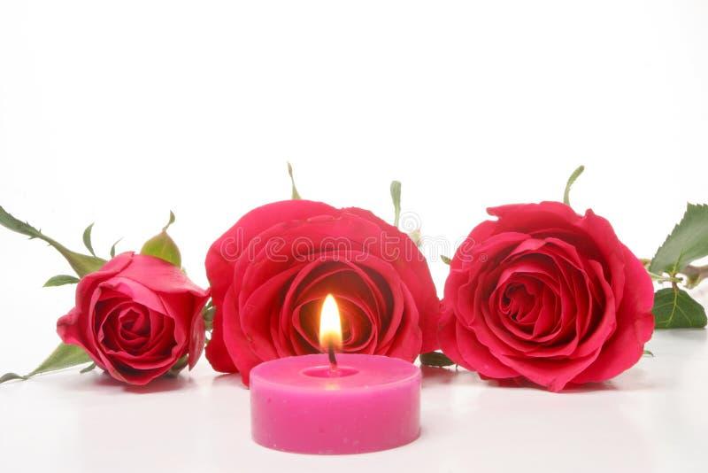 Kerze und rote Rosen lizenzfreie stockfotografie