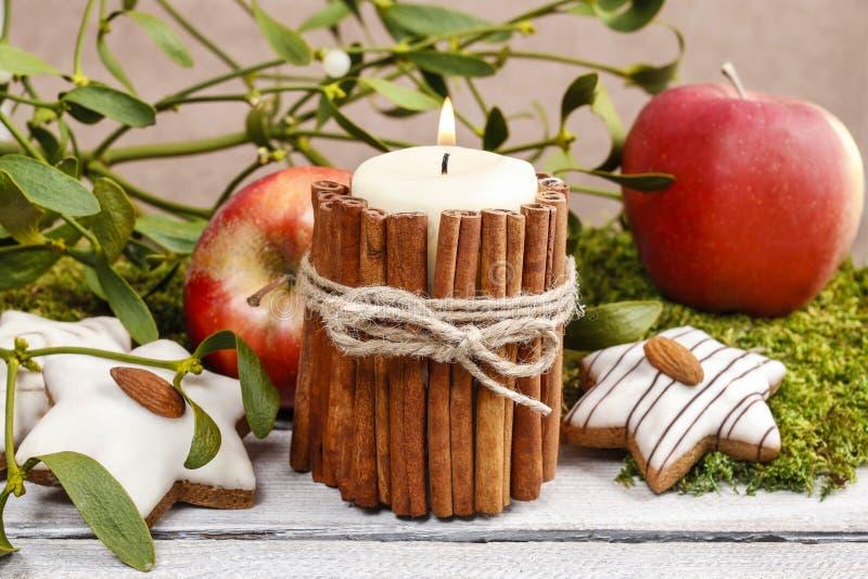 Kerze verziert mit Zimtstangen stockfotografie