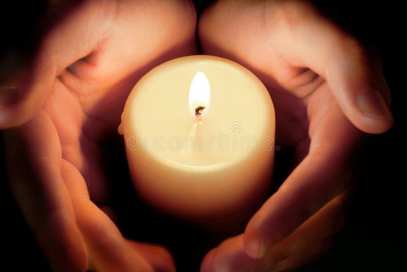 Kerze zwischen den Händen stockfoto