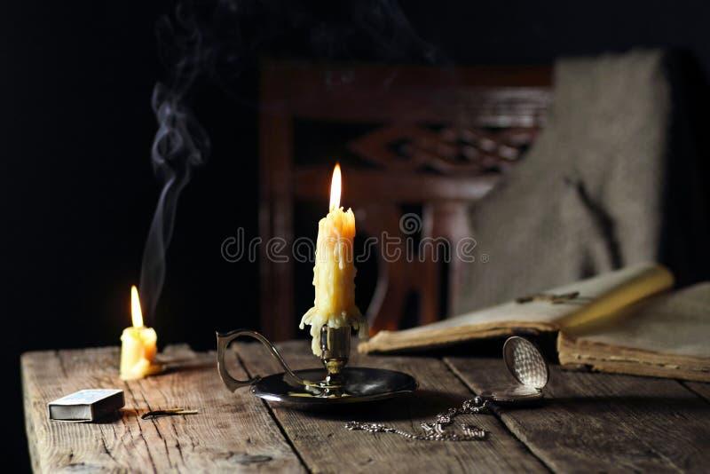 Kerzen auf dem Tisch mit der Buch- und Taschenuhr lizenzfreie stockfotografie