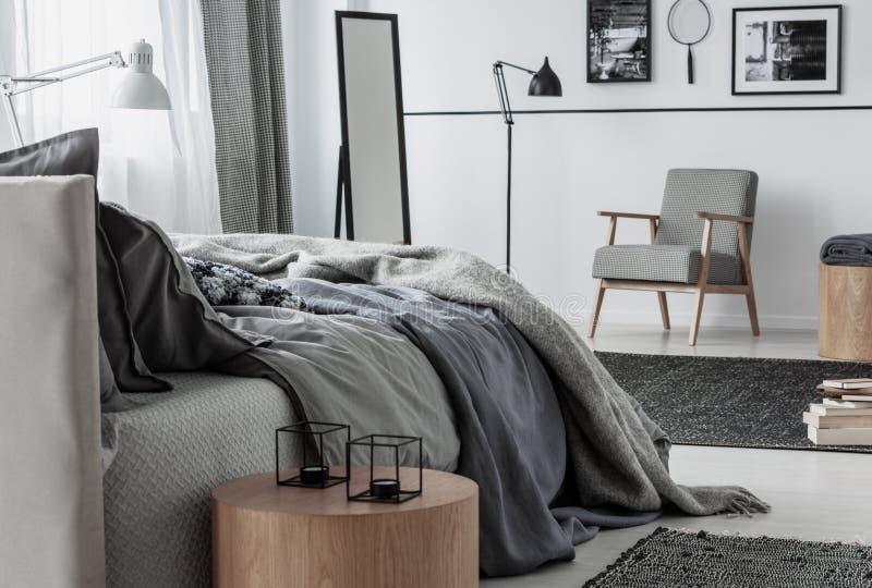Kerzen auf einer Tabelle nahe bei grauem Bett im Schlafzimmerinnenraum mit Lehnsessel und Lampe Reales Foto stockfotos