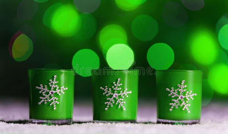 Kerzen, die im Schnee mit defocussed feenhaften Lichtern, grünes bokeh im Hintergrund, festlicher Weihnachtshintergrund stehen stockfoto