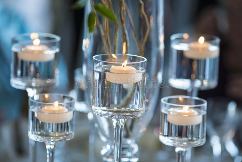 Kerzen, die in Stemware für Hochzeitstafel schwimmen stockbild