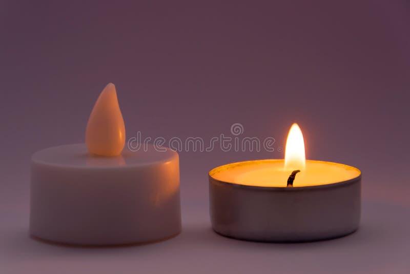 Kerzen-Fälschung GEGEN wirkliches Konzept lizenzfreie stockfotos