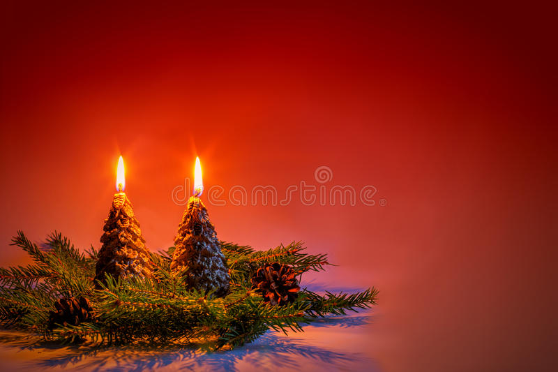 Kerzen in Form der Weihnachtsbäume auf einem roten Hintergrund stockfoto
