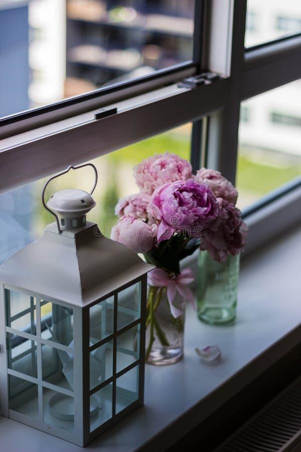 Kerzen-Laterne nahe purpurroter Petaled Blume auf Glasfenster stockbilder