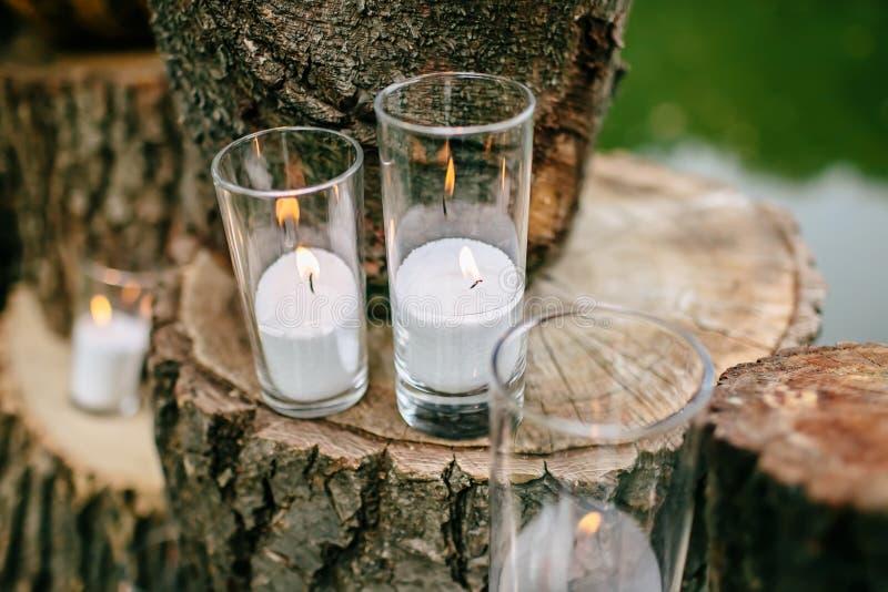 Kerzen in verzierten Bechern Hochzeitsdekorationen in der rustikalen Art Ausflugzeremonie Heirat in der Natur stockbilder
