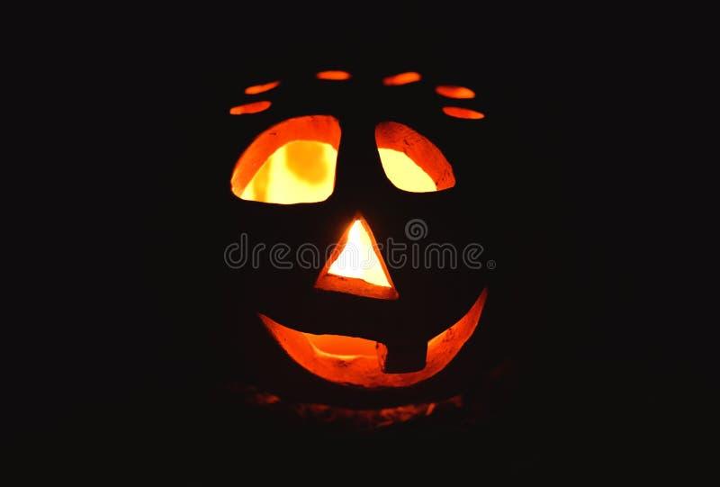 Kerzenständerkürbis mit einem brennenden Kerzeninnere auf dunklem Hintergrund, Symbol von Halloween stockfotos