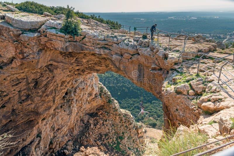 Keshet grotta Israel Women som rappelling och hänger som är uppochnervänd i båge royaltyfri fotografi