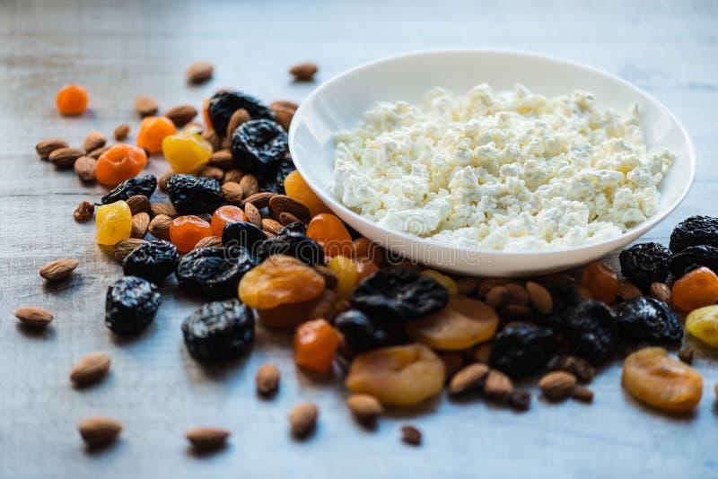 Keso i den vita maträtten Katrinplommoner, torkade aprikors, torkade mandariner och mandlar på en ljus träbakgrund royaltyfri fotografi