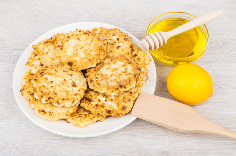 Kesopannkakor i platta, honung och citron på tabellen arkivbild