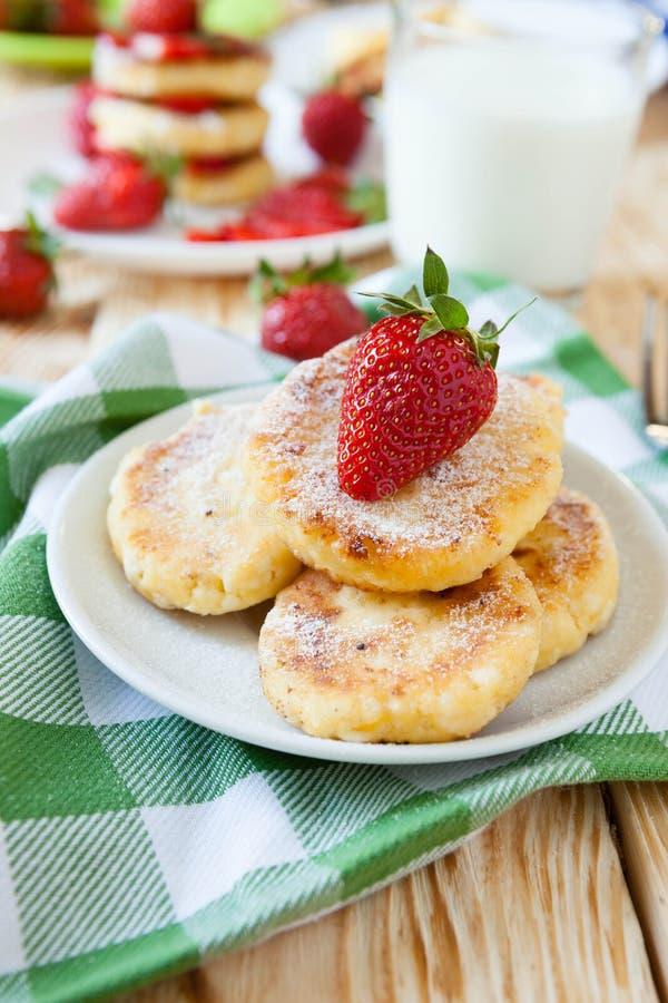 Kesopannkakor med mogna jordgubbar arkivbild