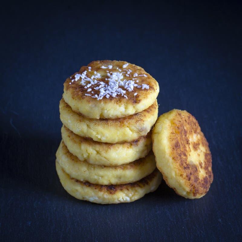 Kesopannkakor med russin, kokosnöt gå i flisor, syrnikien på svart bakgrund royaltyfria foton