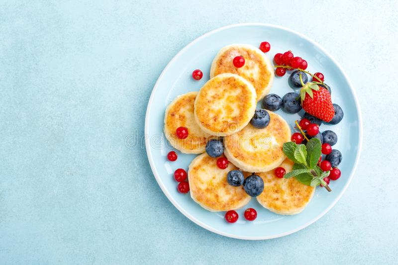 Kesopannkakor, syrniki med nya b?r f?r frukost royaltyfria bilder