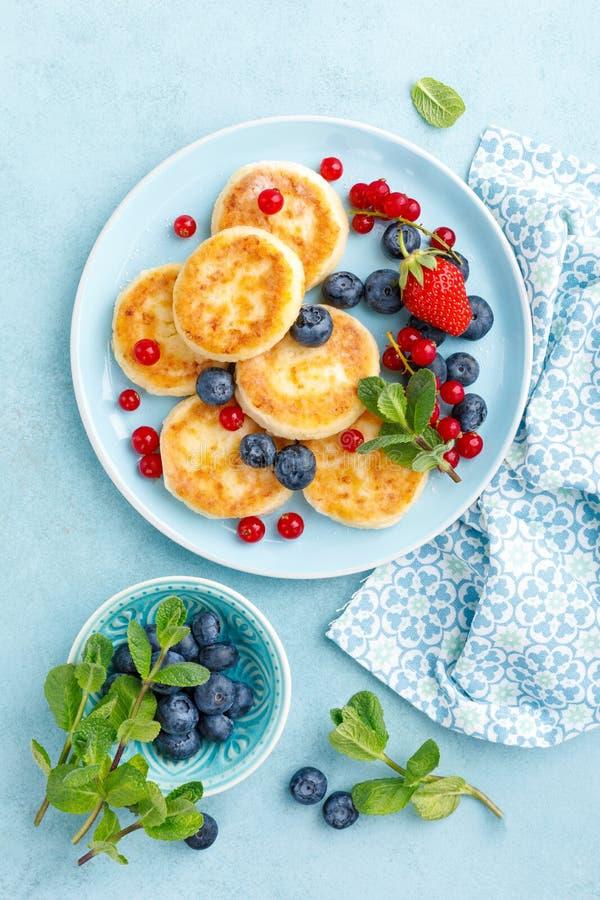 Kesopannkakor, syrniki med nya b?r f?r frukost arkivbilder