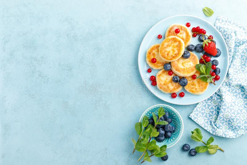 Kesopannkakor, syrniki med nya b?r f?r frukost royaltyfri foto