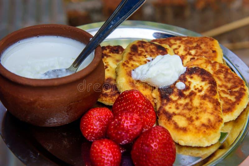 Kesopannkakor/syrniki-/ostmassastruvor med ny jordgubbar och kr?m Traditionell ukrainsk och rysk frukost royaltyfri fotografi